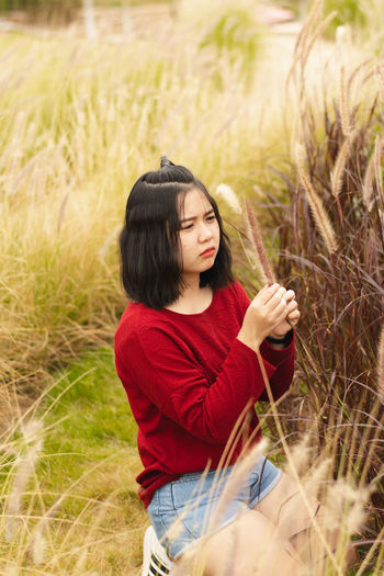 Young woman looking at plant while kneeling on field