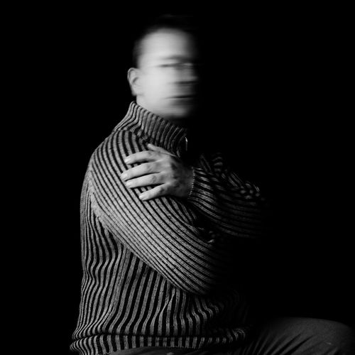 Man shaking head while sitting with arms crossed against black background