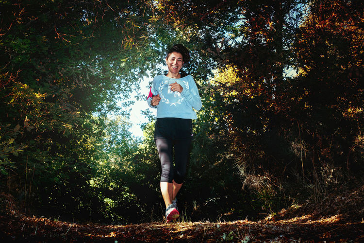 Full Length Portrait Of Woman Jogging On Field