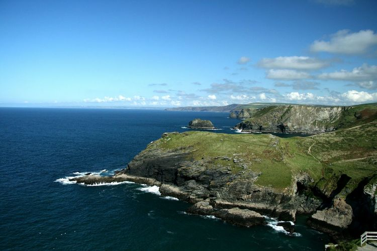 Scenic view of cliffed coast against blue sky