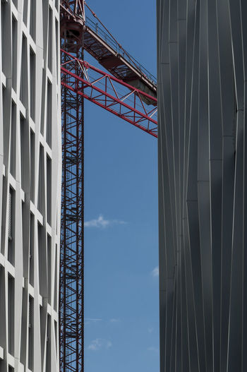 Low angle view of buildings and crane against sky