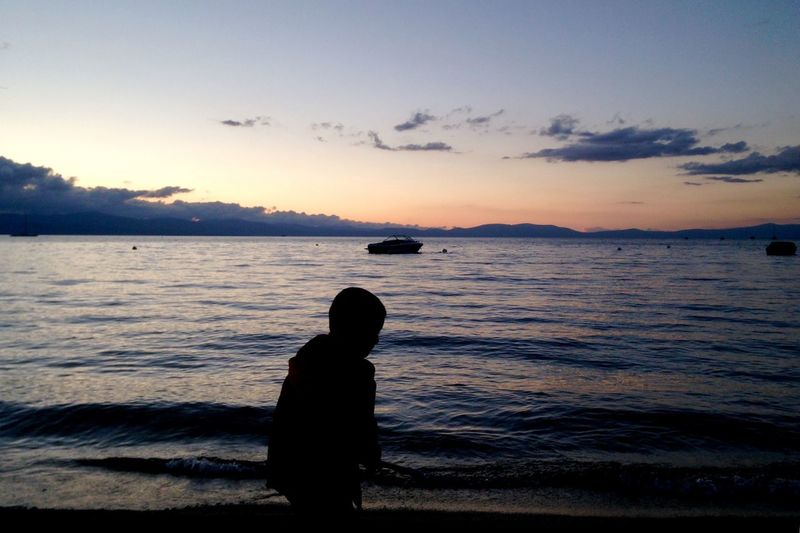 Silhouette boy standing at beach against sky during sunset