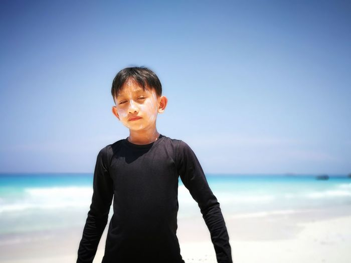 Boy standing on shore at beach against sky during sunny day