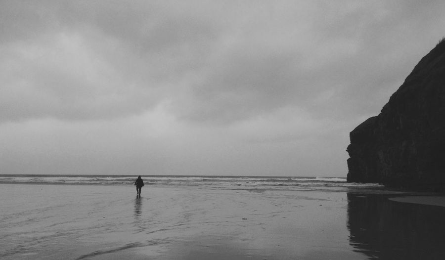 Rear view of silhouette person standing on beach