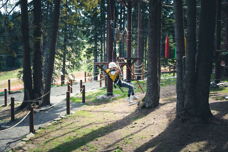 Carefree boy zip lining and having fun after roper course in the forest.