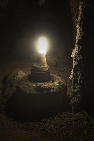 In the Dark Cave. Bulb Burning Cave Close-up Dark Dark Darkness And Light Fire - Natural Phenomenon Flame Glowing Heat Heat - Temperature Illuminated Lamp Light Lit Nature Night No People Rock Shadow Stalactite  Stalagmite