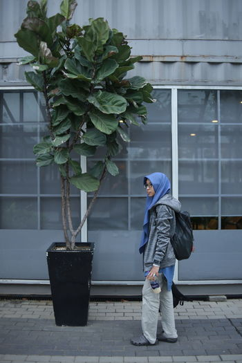 Full length of woman standing against potted plants