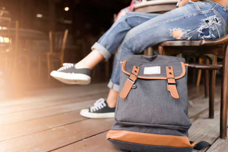 Backpack with traveler for travel concept One Person Sitting Focus On Foreground Real People Casual Clothing Table Lifestyles Leisure Activity Midsection Wood - Material Men Low Section Day Bag Musical Instrument Women City Holding Human Body Part Jeans Travel Destinations Traveling Waiting Sitting