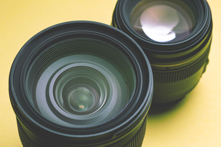 close up of dslr lens on yellow background Photography Themes Camera - Photographic Equipment Photographic Equipment Close-up Lens - Optical Instrument Technology Indoors  No People Camera Focus On Foreground Digital Camera Glass - Material Circle Still Life Equipment Geometric Shape Yellow Studio Shot Optical Instrument Modern