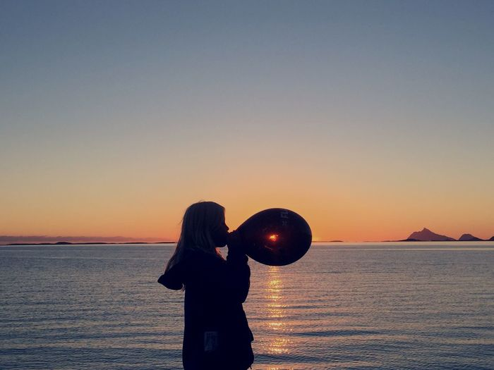 Side View Of Woman Blowing Balloon At Sea Shore Against Sky During Sunset
