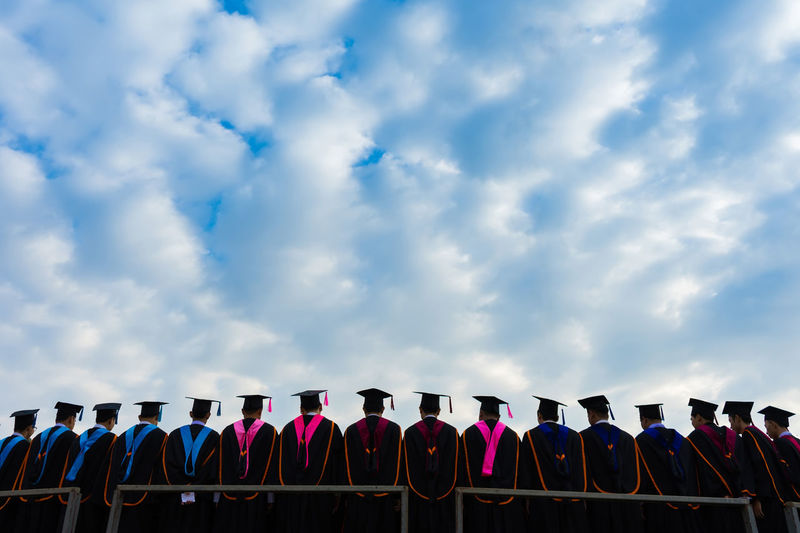 Rear View Of Male Students Standing In Graduation Gowns Against Cloudy Sky