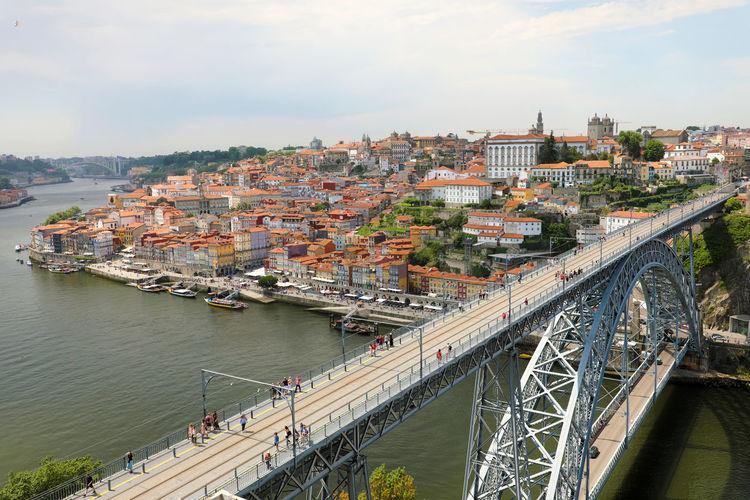 People on dom luis i bridge over douro river in city