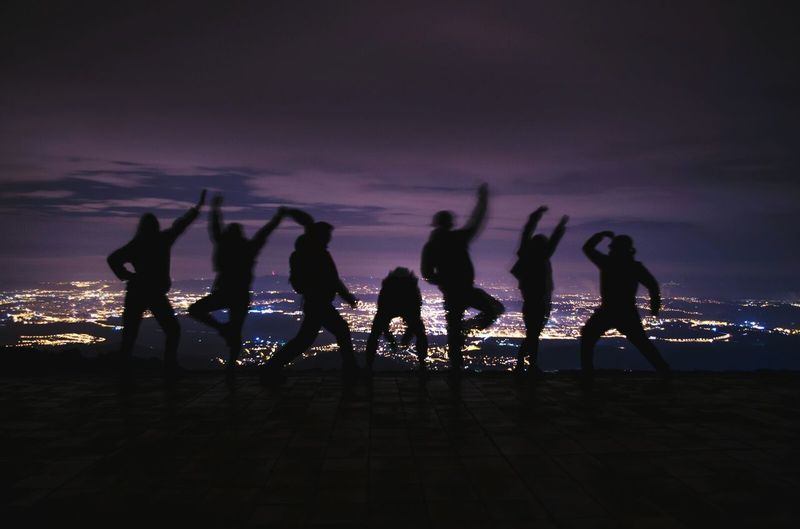 Silhouette friends gesturing against illuminated city at night