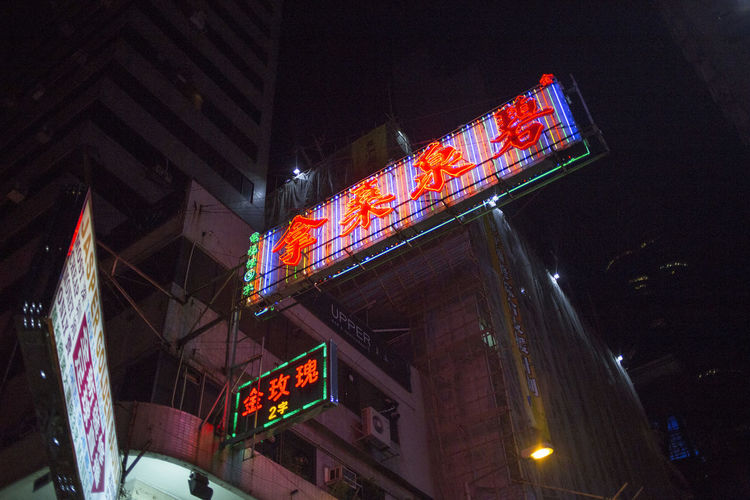 Low angle view of illuminated text on building at night