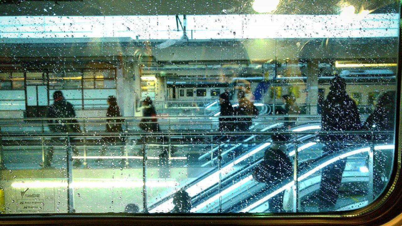 PEOPLE SEEN THROUGH WET GLASS WINDOW