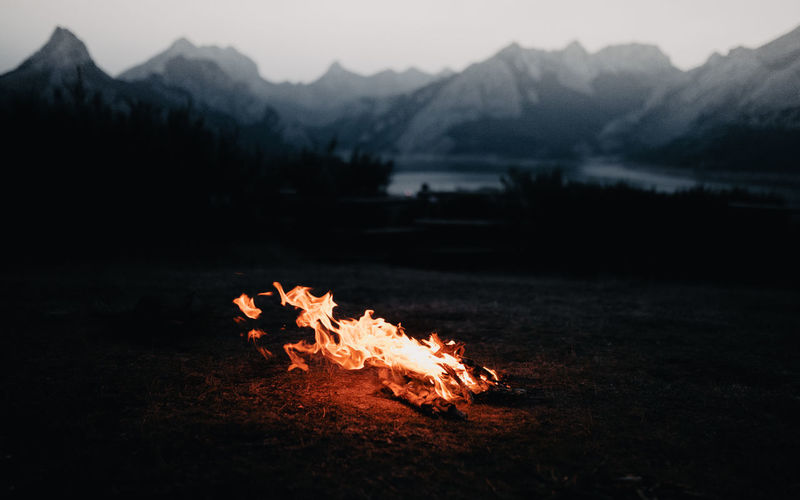 Bonfire on field against mountain range