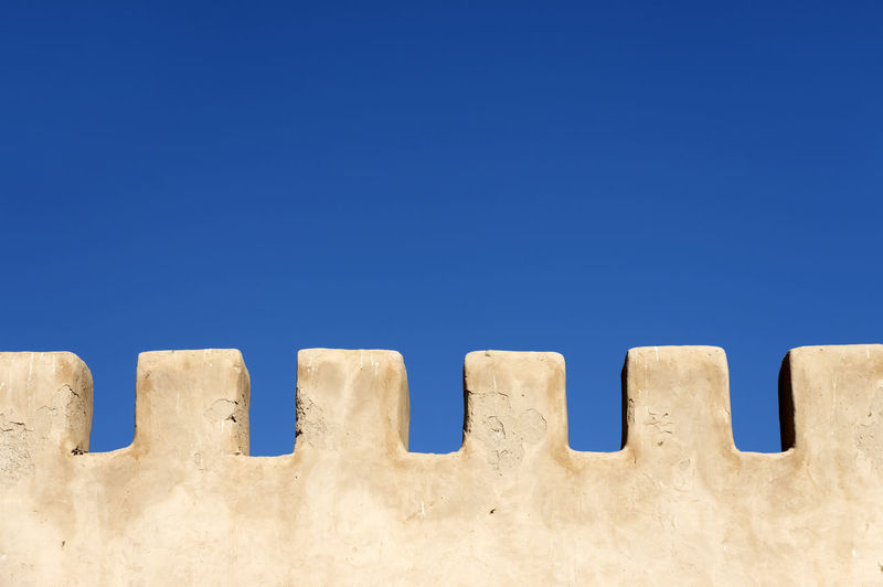 Close-up of white wall against blue sky