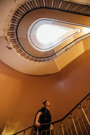 Low angle view of man standing on staircase in building