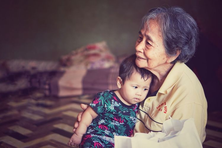Grandmother With Baby Girl Sitting At Home