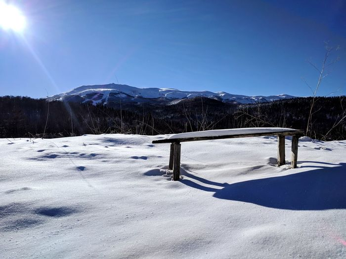 Wooden bench in the mountains. Sunny Bench Sunrays White Snow Winter Cold Temperature Mountain Nature Landscape Mountain Range Weather Scenics Frozen Sky Beauty In Nature Day Snowcapped Mountain Outdoors Snowing No People Clear Sky