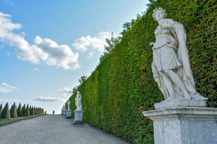 Statue amidst plants against sky