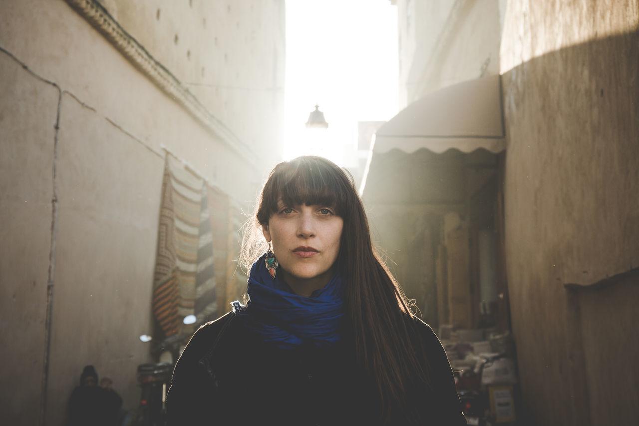 Woman standing on narrow street