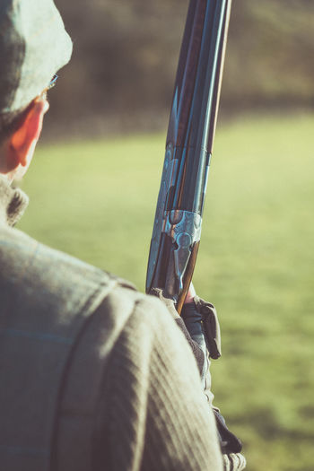 A man holding a shotgun whilst out pheasant shooting. Country Living Gun Pheasant Shoot Pheasant Shooting Winter Close-up Country Life Countryside Day Focus On Foreground Men Nature One Person Outdoors People Real People Shooting Rifle Shotgun Shotguns