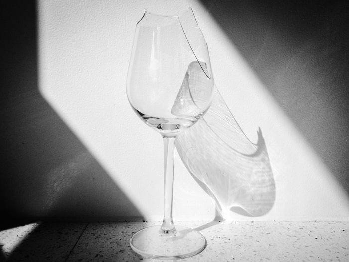 Close-up of wineglass by wall