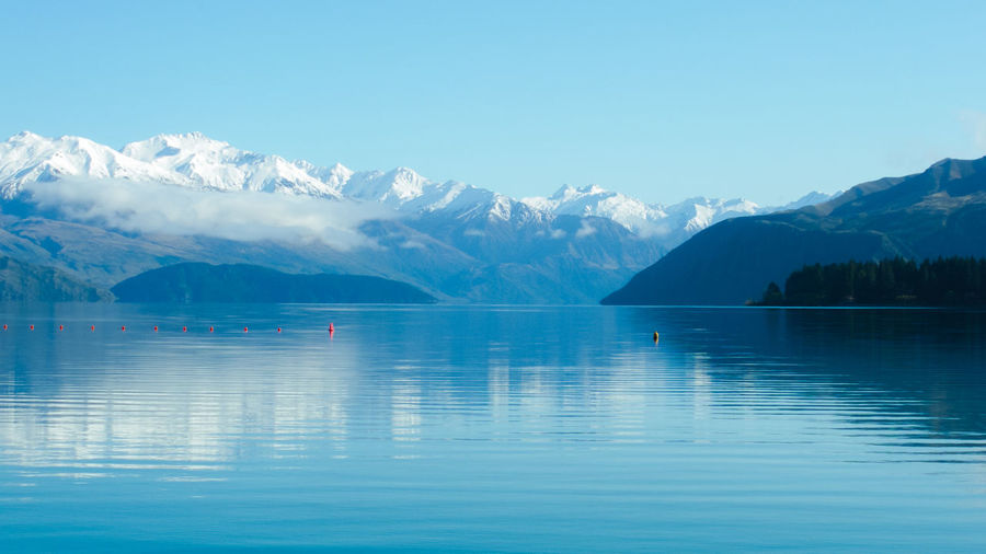 Red bouys contrasting the Wanaka Lake and Mountain cool blues Beauty In Nature Blue Clear Sky Cold Temperature Idyllic Lake Mountain Mountain Range Nature No People Reflection Scenics - Nature Sky Snowcapped Mountain Tranquil Scene Tranquility Water Waterfront Calm Lakeside Non-urban Scene