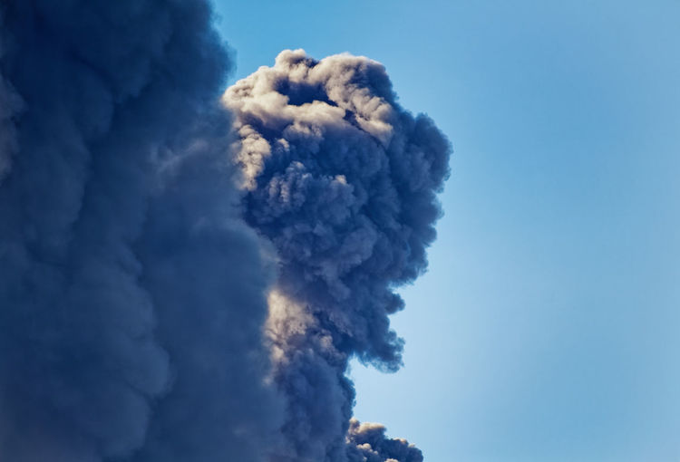 Low angle view of smoke emitting from volcanic against blue sky