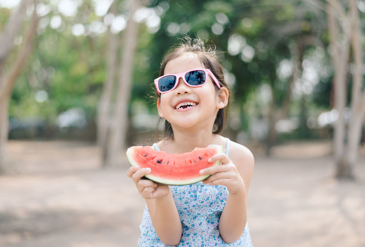 Cute smiling girl holding watermelon