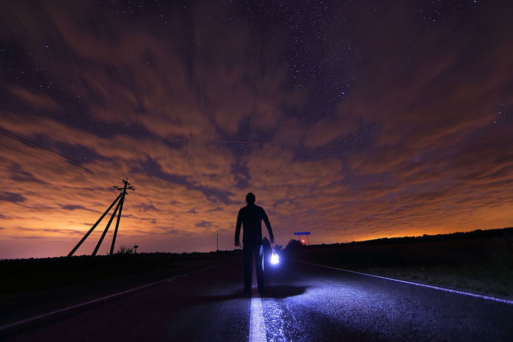 Silhouette man carrying torch light standing on road against cloudy sky