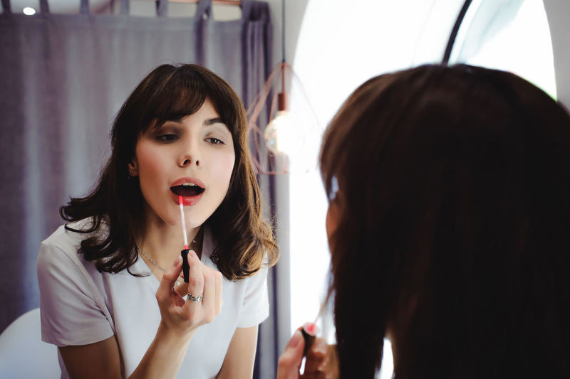 Close-Up Of Young Woman Applying Red Lipstick In Front Of Mirror At Home