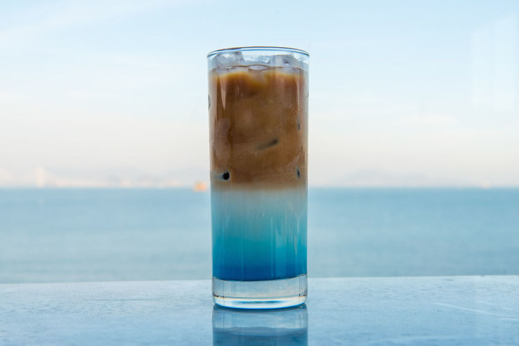 Drinking Glass Drink Glass Food And Drink Refreshment Water Household Equipment Focus On Foreground Table Transparent No People Sea Close-up Freshness Day Horizon Over Water Glass - Material Horizon Sky Non-alcoholic Beverage