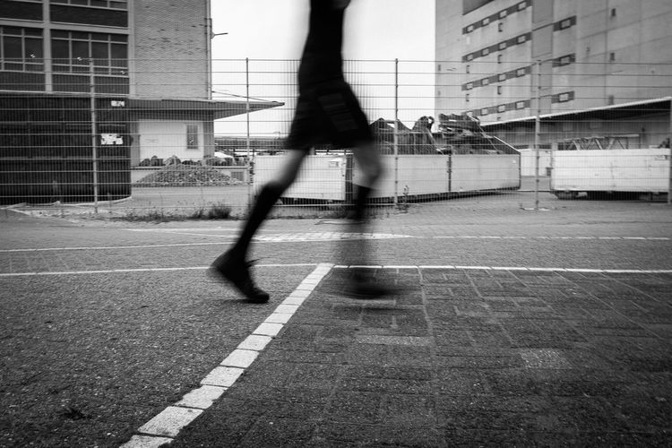 Low section of man running on street in city
