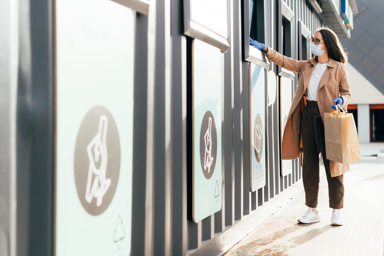 Woman standing by text on wall