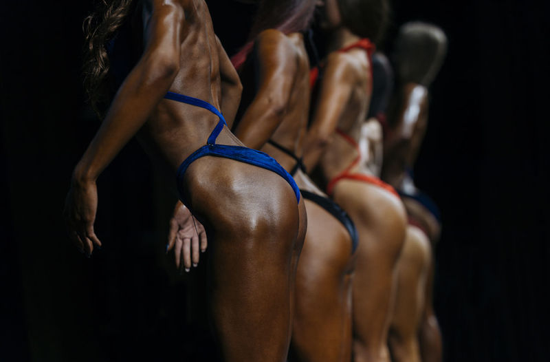 Midsection of body builders standing during competition