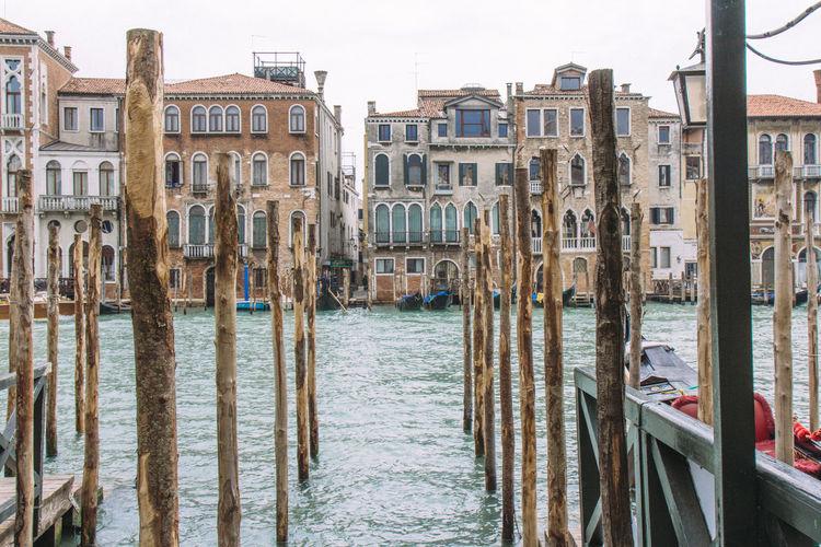Wooden poles in river against buildings