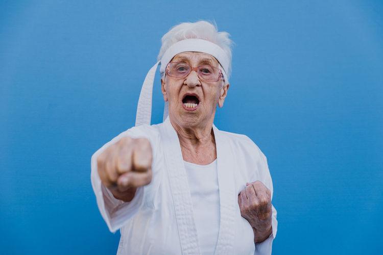 Portrait of senior woman doing karate against blue background