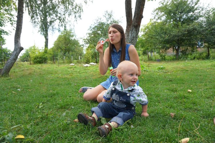 village garden#10 Baby Babyhood Casual Clothing Childhood Day Field Full Length Grass Growth Holding Lifestyles Nature Outdoors Pacifier Park - Man Made Space People Real People Sitting Sky Togetherness Tree Two People Young Adult