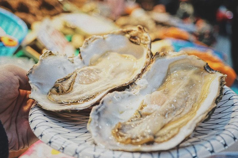 SHELLFISH  Oyster  Seafoods EyeEm Selects Food Food And Drink Freshness Close-up Seafood Indoors  Plate Market One Person Healthy Eating Human Hand Ready-to-eat People Day