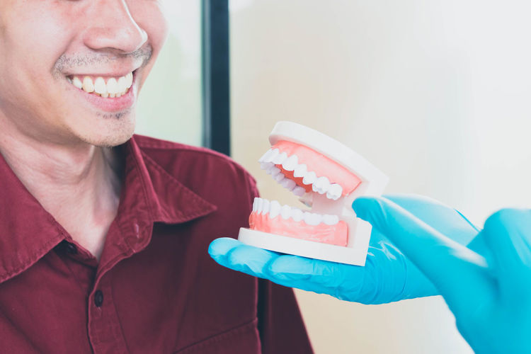 Cropped hands showing dentures to patient