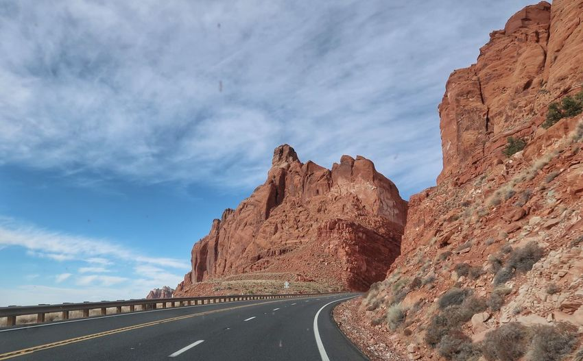 Landscape of road leading up between red cliffs in Arizona Sky Road Cloud - Sky The Way Forward Direction Transportation Nature Beauty In Nature No People Symbol Scenics - Nature Rock Day Tranquility Non-urban Scene Tranquil Scene Rock - Object Marking Rock Formation Mountain