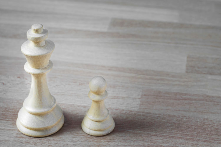 Close-Up Of Chess Pieces On Wooden Table