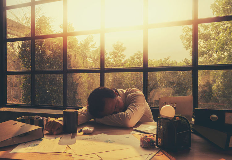 A tired young businessman Until causing himself to run down to sleep on the desk For business success Window One Person Table Indoors  Real People Glass - Material Nature Men Sitting Day Lifestyles Food And Drink Paper Transparent Furniture Drink Cup Relaxation Sunlight Glass Tired! Businessman