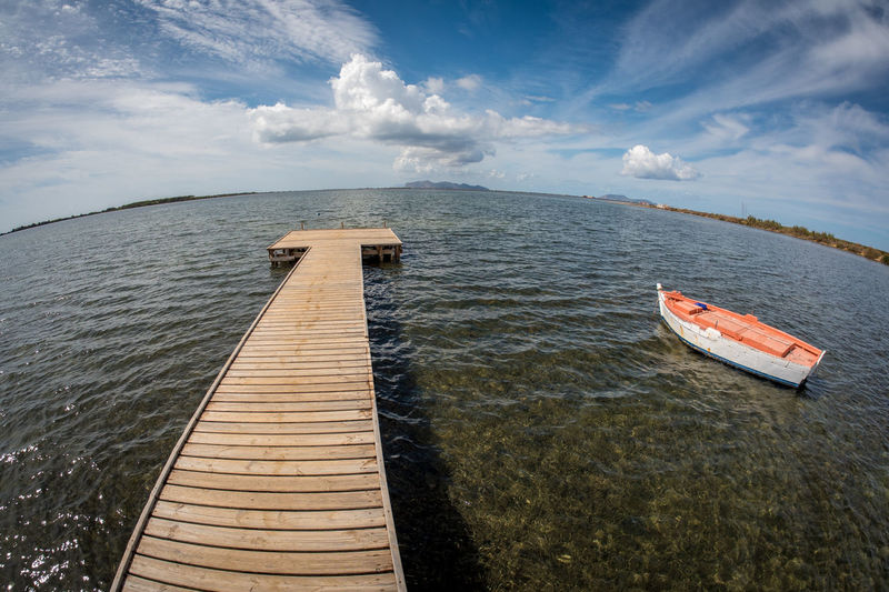 Fish-eye view of jetty in sea against sky