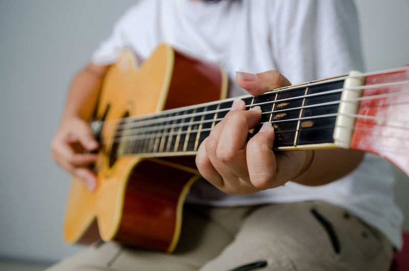Midsection of woman playing guitar