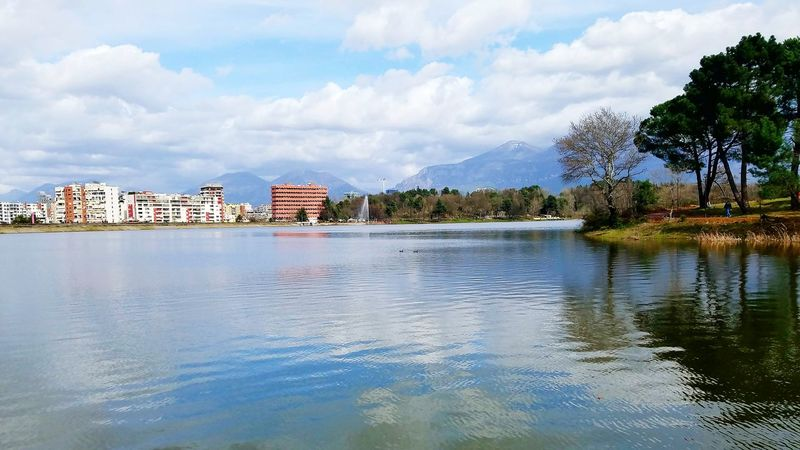 Beauty In Nature Mountain Range Mountain In The Background Clouds And Sky Artificial Lake Of Tirana Colorful Green Color Cityscape Buildings Naturelover Trees And Nature Trees Reflections In The Water Lake View Summer Exploratorium