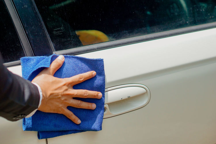 Midsection of person with umbrella on car window