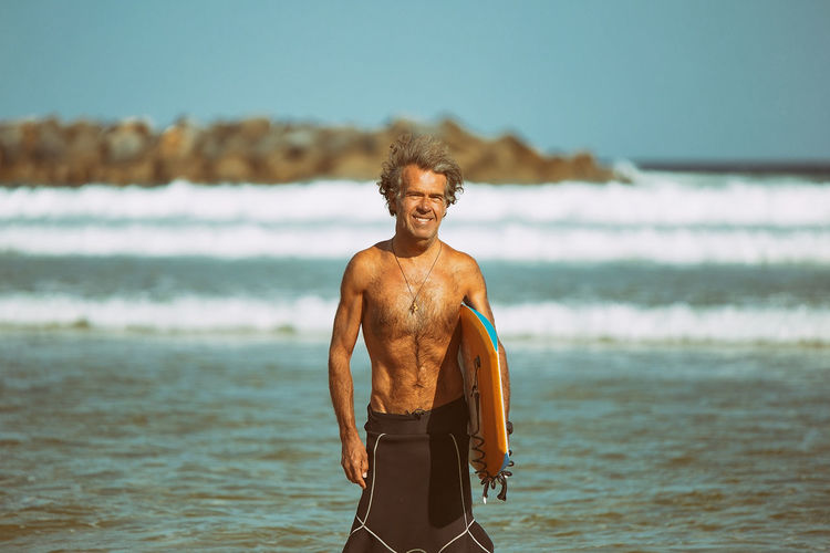 Portrait of shirtless man standing on beach